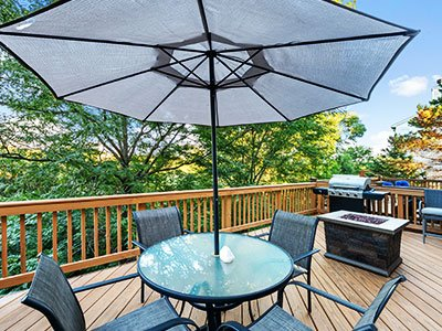 Composite deck with barbeque, fire feature, glass table, metal chairs, gray umbrella, and tall trees in the background.