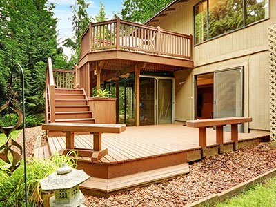 Composite deck with stairs, a wooden bench, and tall trees in the background.