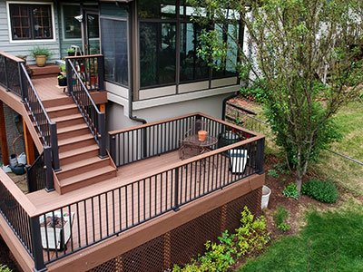 Composite deck with stairs, metal bars, house with large dark windows, and simple landscaping.