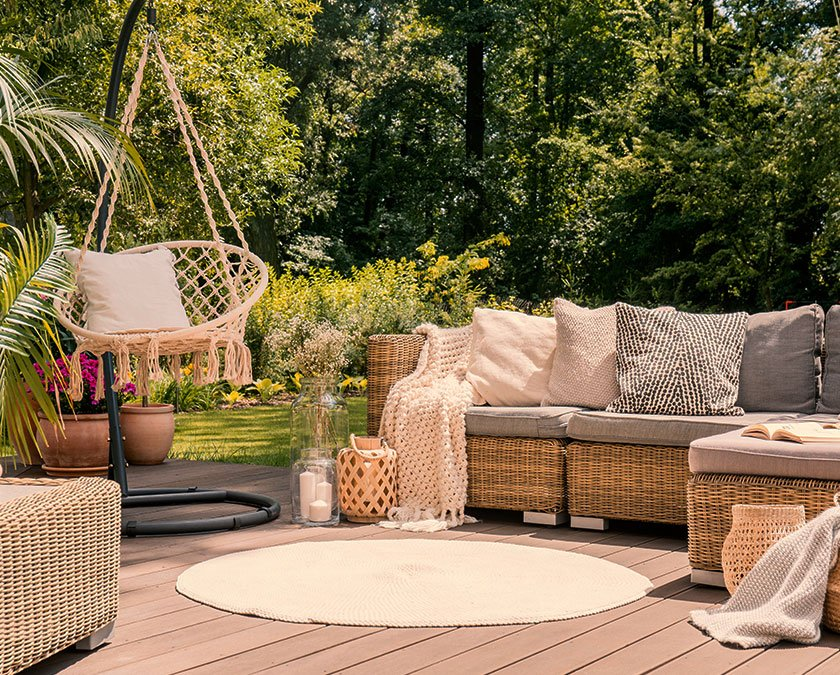 Backyard hardwood deck with a beige carpet, rattan couch, mesh swing, pillows and blanket, and trees in the background.