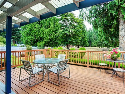 Hardwood deck with metal cover, glass table, metal chairs, and trees in the background.