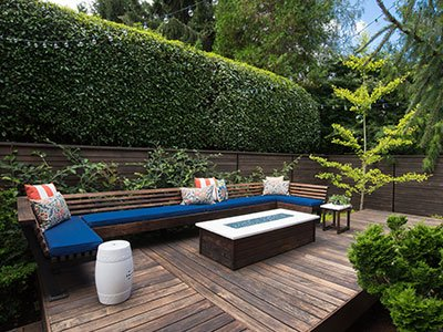 Hardwood deck with dark wooden couch, blue pillow seats, white glass coffee table, and lots of trees and shrubs around.