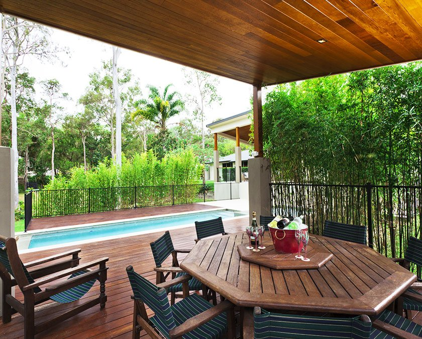 Hardwood deck with wooden cover, wooden table and chairs, lush greenery nearby, and a pool.