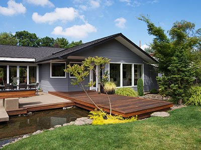 Hardwood deck with pond nearby, gray siding house, and tall trees in the background.
