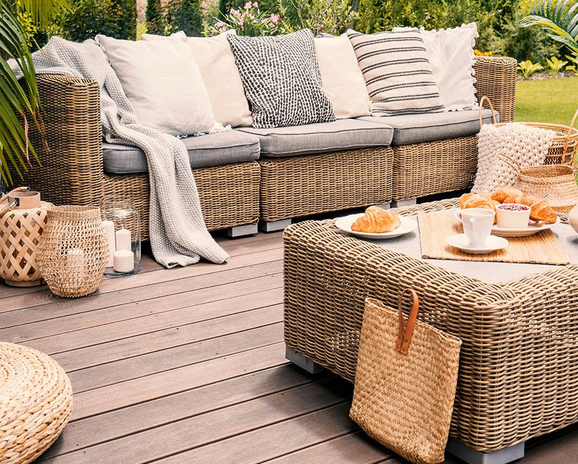 Hardwood deck with rattan couch and table, decor items, plate with croissants, and cups of coffee.