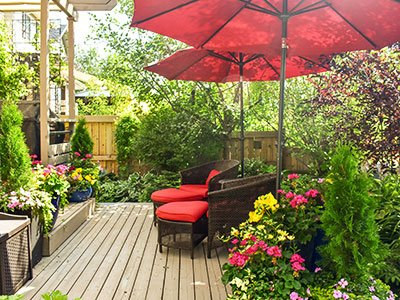 Small hardwood deck with rattan chairs, colorful flowers, green plants around, and red umbrellas.