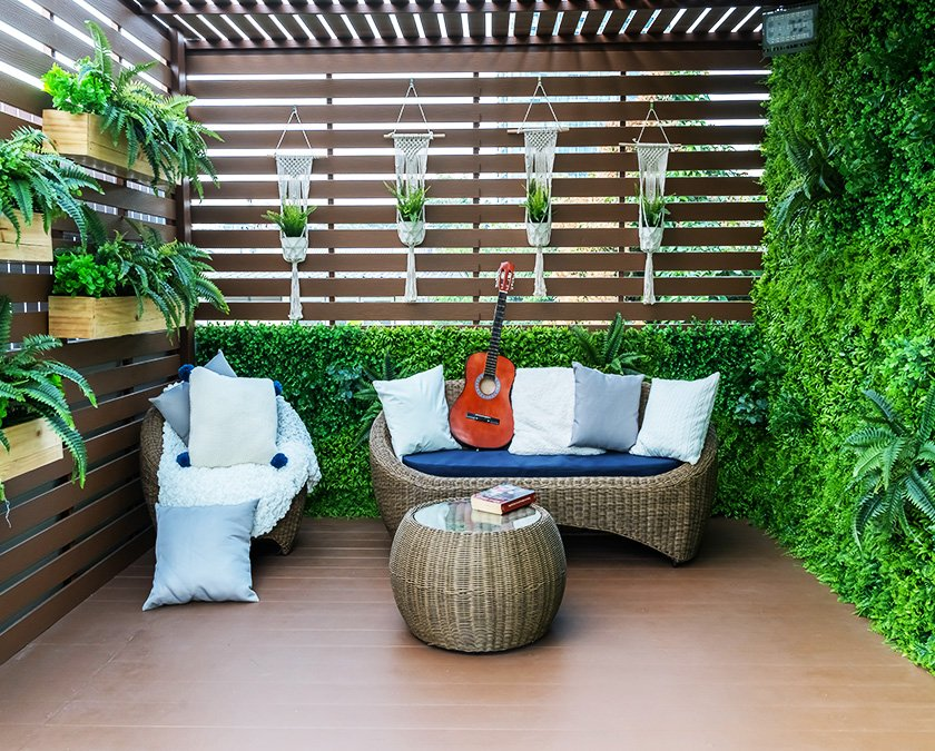 Composite deck with hardwood cover, green plants decor, rattan couch and chairs, white and blue pillows, and a reddish guitar on the couch.